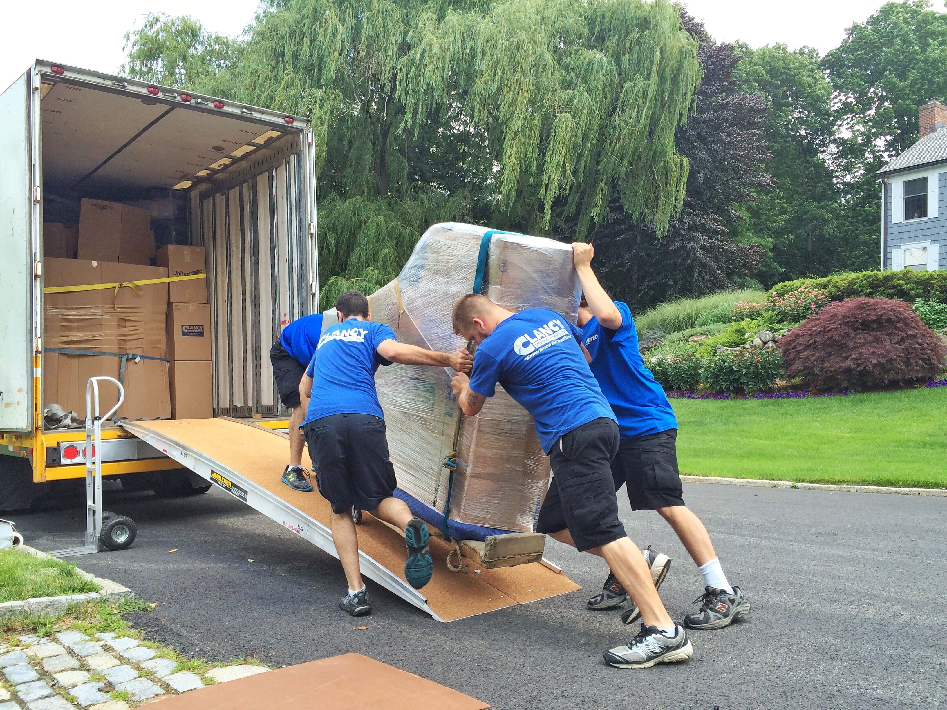 Movers pushing piana onto moving truck